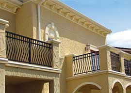 Exterior features include wrought iron railing, heavy decorative stucco and distinctive architectural details